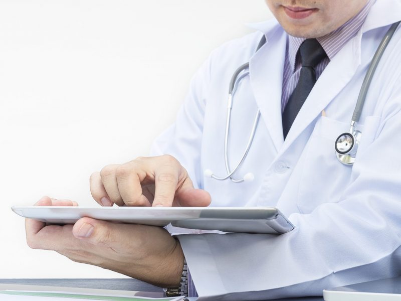 Doctor is working with tablet over white background